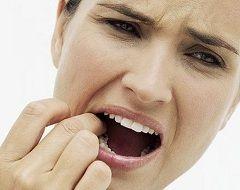 Біль при натисканні на інфікований зуб - один із симптомів остеомієліту щелепи